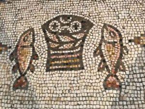סלסלת הלחם ושני הדגים בצידה ברצפת המוזיאיקה בכנסיית הלחם והדגים בטבחה